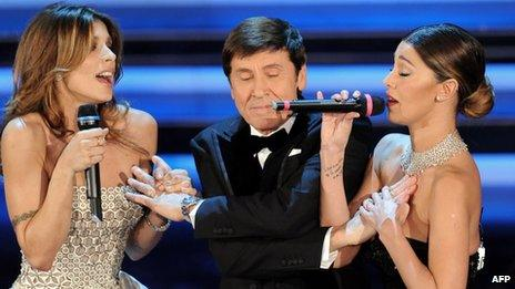 Argentinian model Belen Rodriguez (R), Italian singer Gianni Morandi (C) and Italian model Elisabetta Canalis at the San Remo festival (14 Feb 2012)