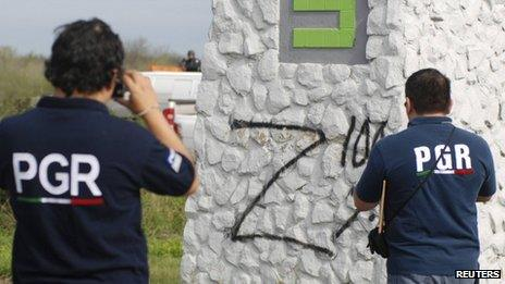 Federal agents take photographs of a Z sprayed onto a wall near a crime scene in Cadeyreta
