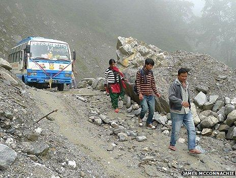 Three people walk downhill in front of a bus