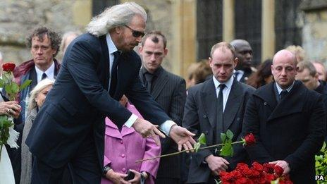 """Barry Gibb releases a rose onto his brother""""s grave"""