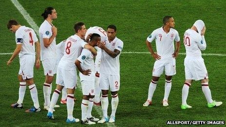 The England football team console Ashley Cole on the pitch in Kiev as his penalty is saved by Italy's goalkeeper