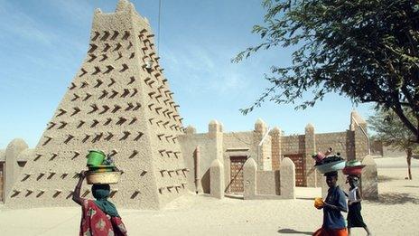 Women walk in front of Timbuktu's Djingareyber Mosque