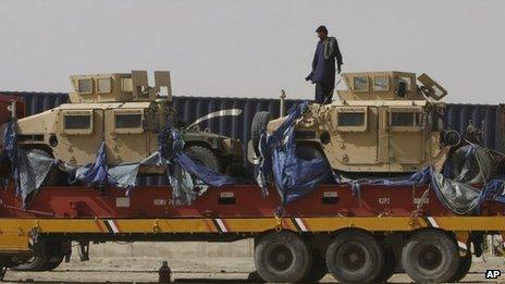 A driver stands on top of a truck carrying Nato Humvees at a terminal in the Pakistani-Afghan border, in Chaman, Pakistan, Wednesday, July 4, 2012.