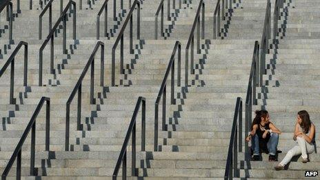 Two young women sit on the steps of the Olympic stadium