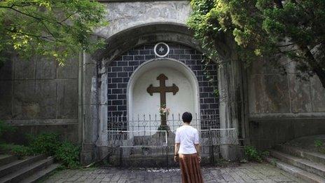 A woman prays outside the Sheshan Catholic Church in Shanghai