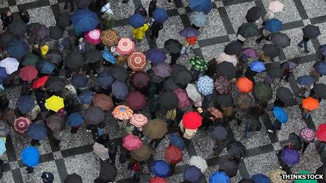 Aerial photo of crowd of people holding umbrellas
