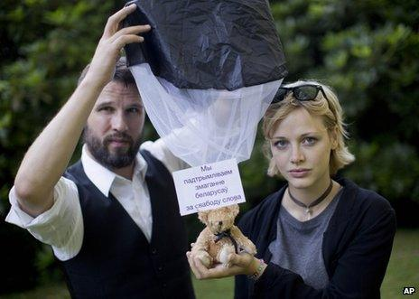 Swedish citizens Tomas Mazetti (left) and Hannah Frey show a teddy bear on a parachute as they pose for a photo in Berlin, 1 August