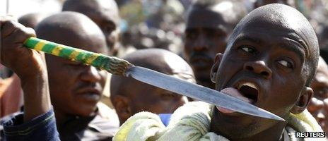A protester licks his spear at the Lonmin-owned mine in South Africa (16 August 2012)