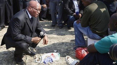 """South Africa""""s President Jacob Zuma, left, interacts with striking mine workers at the Lonmin mine near Rustenburg, South Africa, Wednesday, Aug. 22, 2012."""