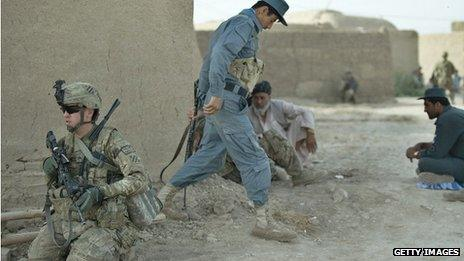 A NATO soldier works with a member of the Afghan National Police