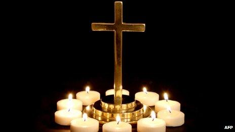 Gold cross surrounded by candles