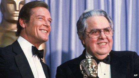 """Albert """"Cubby"""" Broccoli, producer of the """"James Bond"""" series, holds the Thalberg Award he received for his work at the Academy Awards, in Los Angeles. Roger Moore, left, British actor who plays secret agent 007 James Bond, made the presentation."""