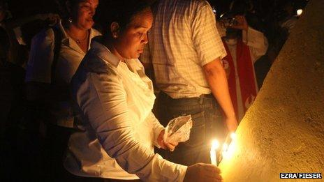 Woman lights candle during events commemorating the 75th anniversary of the massacre