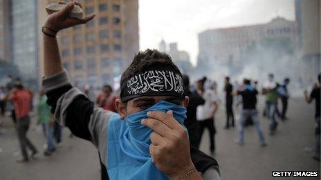 A supporter of the March 14 movement throws stones towards Lebanese security forces