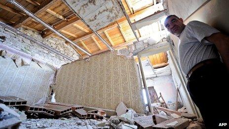 L'Aquila resident stands in their devastated house