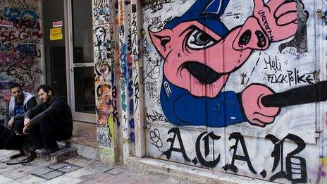 Athenians sitting in front of anti-government graffiti