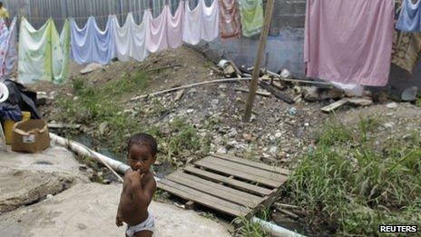 A child stands next to a clothes line in the low income neighbourhood of Curundu in Panama City, 27 September 2012