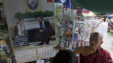 A Buddhist monk looks at a calendar with photographs of American President Barack Obama and Myanmar's opposition leader Aung San Suu Kyi