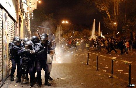 Spanish riot police protect themselves after coming under attack in Madrid, 14 November