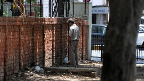 Man urinating against wall