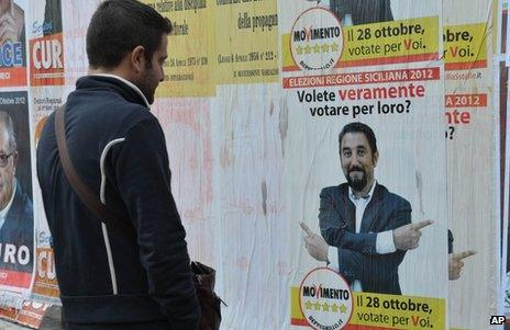 A man looks at a Five Star Movement poster during a local election campaign in Sicily, 28 October