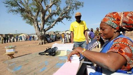 An electoral officer gives ballot papers to a voter upon his arrival at Bole polling station in Ghana's northern region on December 7, 2012.