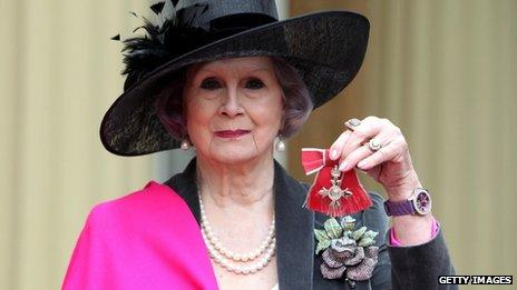 April Ashley holds her MBE medal