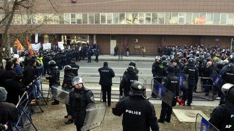 """The police create a cordon between the supporters of the conservative government, left and the supporters of the opposition, right, who are protesting """"pro"""" and """"against """" the national budget, in Skopje, Macedonia"""