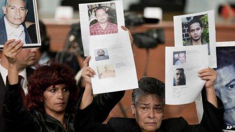 People hold up photographs of alleged victims of crime during an event at which President Pena Nieto enacted the crime victims law