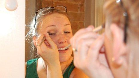 Jillian Rae Greenwood applying make up in the mirror