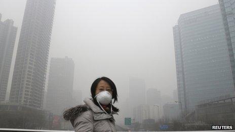 A woman wearing a mask walks on a pedestrian bridge on a hazy day in Beijing