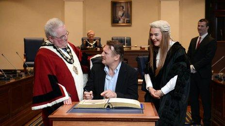 Liam Neeson signs the book of burgesses