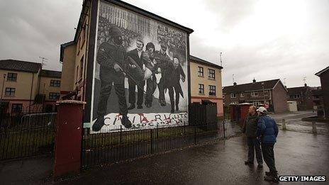 Two men looking at mural depicting the events of Bloody Sunday in Londonderry, 1972