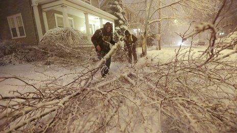 Residents clear a fallen tree from the road in New Bedford, Massachusetts 8 February 2013
