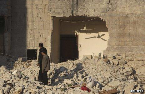 Men inspect the rubble of homes in Aleppo, Syria, 13 February