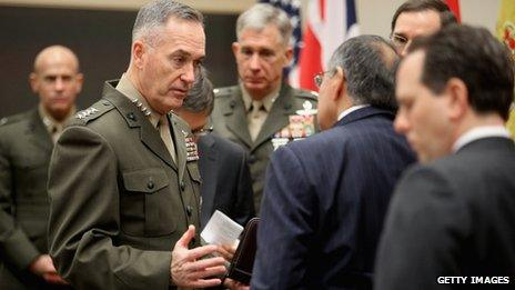 General Joseph Dunford Jr (centre) talks to US Defence Secretary Leon Panetta after they arrive at the Nato headquarters in Brussels 21 February 2013