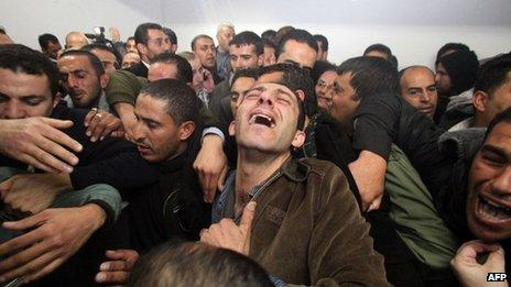 Palestinian relatives and friends mourn Arafat Jaradat, who died in an Israeli prison, after his body was handed over by Israeli authorities on Sunday at a hospital in the West Bank city of Hebron