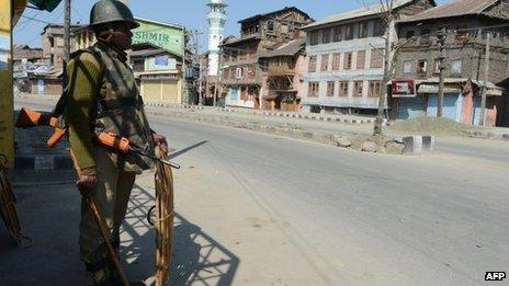 An Indian paramilitary trooper keeps watch during a curfew in Srinagar on March 6, 2013