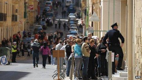 People queue outside a polling station during the National elections of Malta on March 9