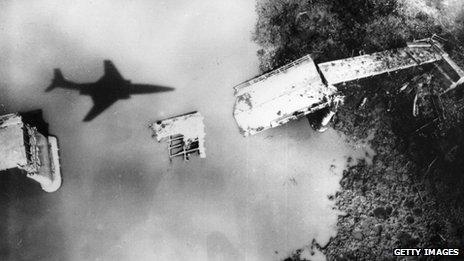 A US jet flies over a destroyed bridge in North Vietnam