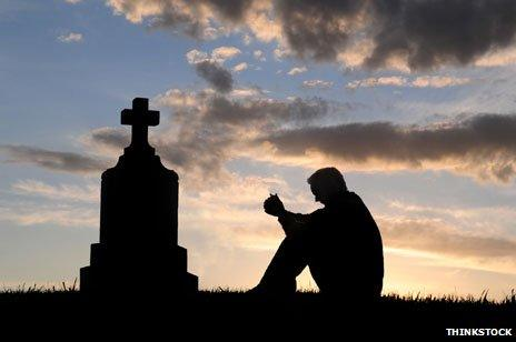 Silhouette of man, sitting contemplatively near a gravestone
