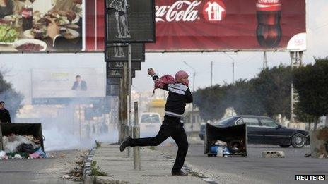 A Palestinian throws a stone at Israeli security forces during a protest in Nablus (18 February 2013)