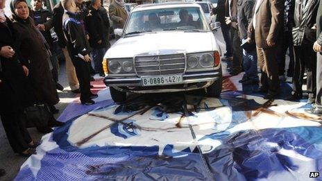A man drives a taxi over a painting of Barack Obama in Ramallah (18 March 2013)