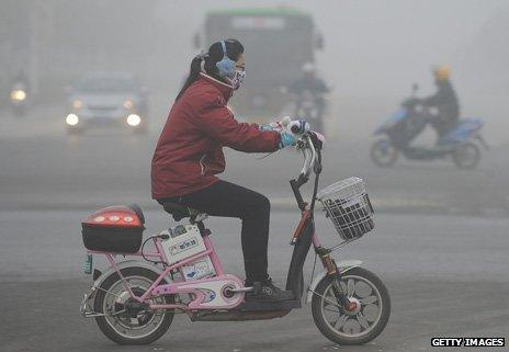 Woman on an electric bike in the smog in Beijing