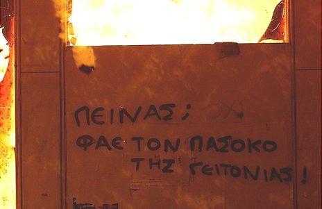 Anti-austerity, anti-Pasok graffiti on burning building