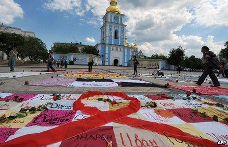 People walk past quilts laying on Mikhaylovskaya Square in Kiev made by HIV positive people to commemorate AIDS victims in Ukraine