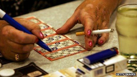 Woman smoking while marking her bingo card