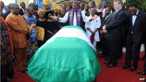 Anglican priest Owen Nwokolo prays in front of the coffin bearing the body of late Nigerian writer Chinua Achebe upon arrival at Abuja airport, on 21 May 2013