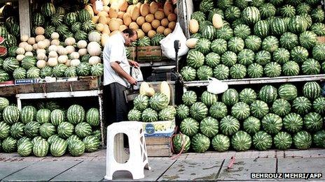 Street vendor selling watermelon in his shop in Sarcheshmeh street in downtown Tehran on June 4, 2013