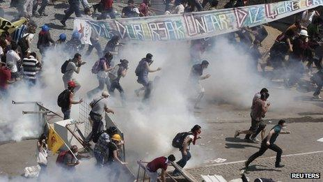 Protesters run as riot police fire teargas during a protest at Taksim Square in Istanbul